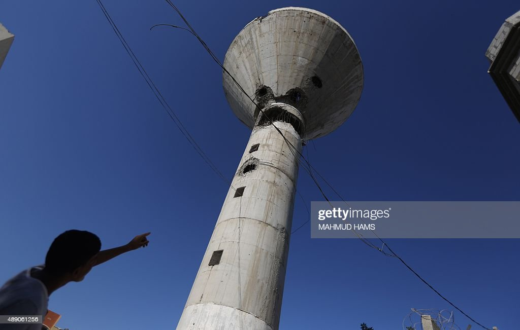 A Palestinian boy points at a water tower targeted by an Israeli air strike overnight in the northern Gaza strip of Beit Hanun on September 19, 2015. Two rockets were fired into southern Israel by Palestinian militants in Gaza, causing no casualties but triggering a series of Israeli air raids.
