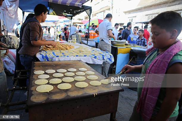Palestinian boy prepares traditional pancakes known as ''Qatayef'' in a street market on the fifth day of the holy month of Ramadan in Rafah in the...