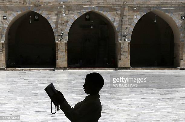 A Palestinian boy reads a copy of the Koran Islam's holy book in a mosque on the first day of the holy fasting month of Ramadan in Gaza City on June...