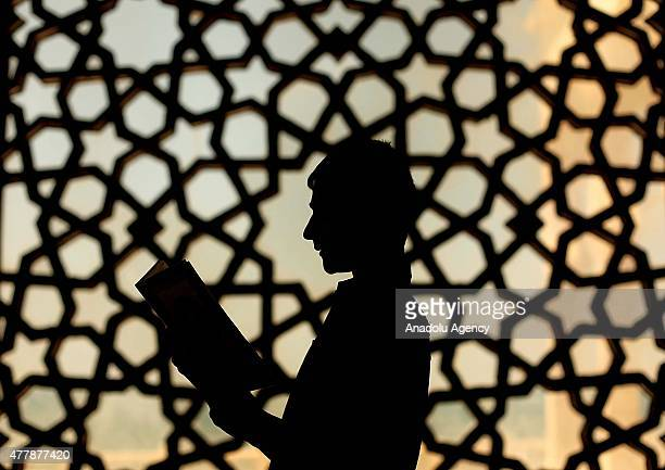 Palestinian boy reads Quran Islam's holy book at AlKhalidi mosque on the third day of Ramadan in Gaza City Gaza on June 20 2015