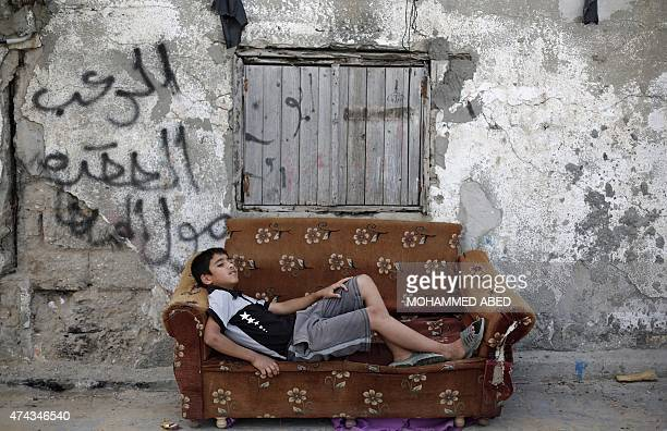 A Palestinian boy rests on an old armchair in front of a dilapidated house on May 22 2015 in Gaza City AFP PHOTO / MOHAMMED ABED