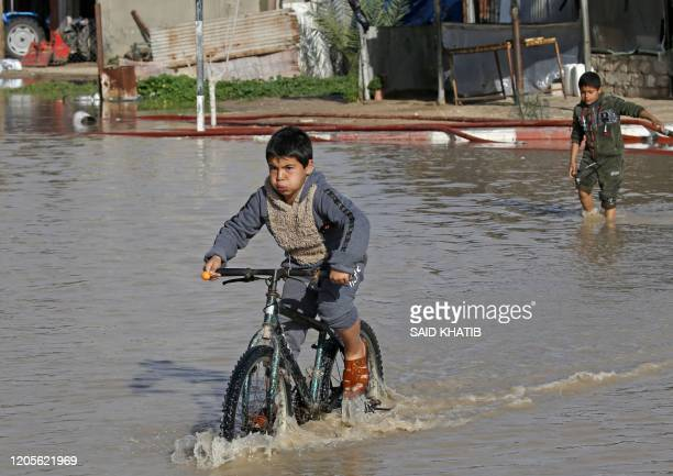 Palestinian boy rides his bicycle through a flooded street in Rafah in the southern Gaza Strip on March 6, 2020.