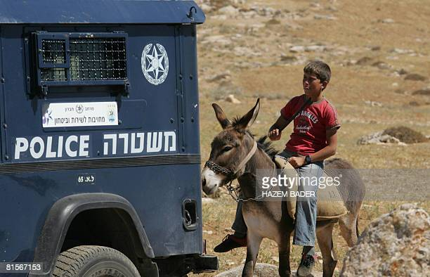 A Palestinian boy rides his donkey past an Israeli police jeep as peace activists hold a demonstration against alleged attacks by Jewish settlers on...