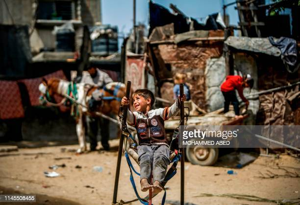 Palestinian boy rides on a makeshift swing in an impoverished area in Beit Lahia in the northern Gaza Strip on May 22 2019