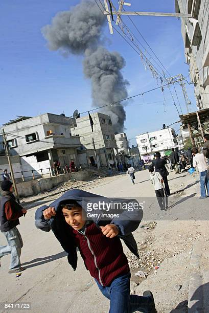 Palestinian boy runs for cover following an Israeli airstrike on January 5 2009 in Rafah southern Gaza Israel is intensifying its widescale ground...