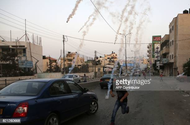 A Palestinian boy runs for cover from tear gas during clashes between demonstrators and Israeli security forces at the Qalandiya checkpoint between...