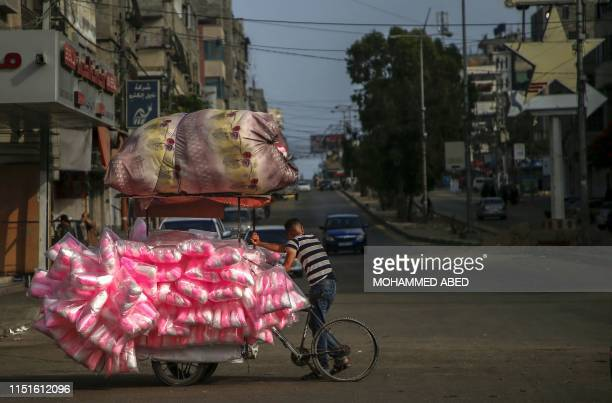 Palestinian boy sells candy floss on a street cart in Gaza City on June 21, 2019. - The United States is set to co-chair a two-day conference in...