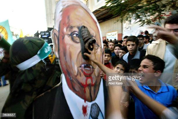 Palestinian boy shouts as he hits with a shoe a portrait depicting Israeli Prime Minister Ariel Sharon as a vampire during a rally to mark the 16th...