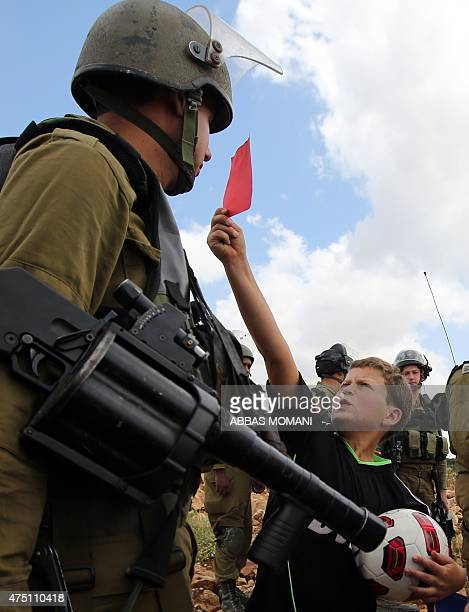A Palestinian boy shows a red card to an Israeli soldier during a rally to show their support for the Palestinian bid to vote the Israel Football...