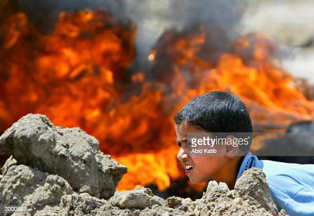 Palestinian boy sits in front of burning tires as he looks at Israeli tanks during an Israeli army operation May 15 2003 in the northern Gaza Strip...