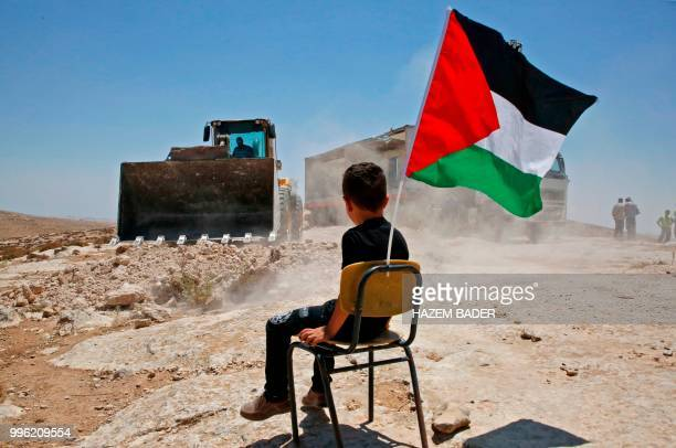Palestinian boy sits on a chair with a national flag as Israeli authorities demolish a school site in the village of Yatta, south of the West Bank...