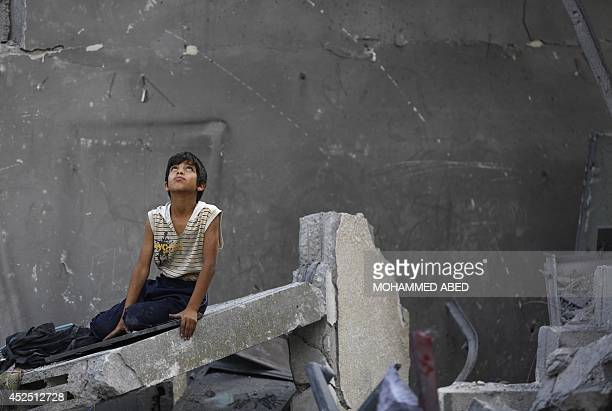 A Palestinian boy sits on the rubble of a destroyed building following an Israeli air strike in the center of Gaza City on July 22 2014 A series of...
