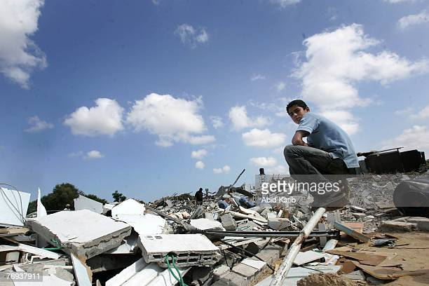 Palestinian boy sits on the rubble of his family house destroyed by Israeli military bulldozers during a military incursion September 21 at the Joher...