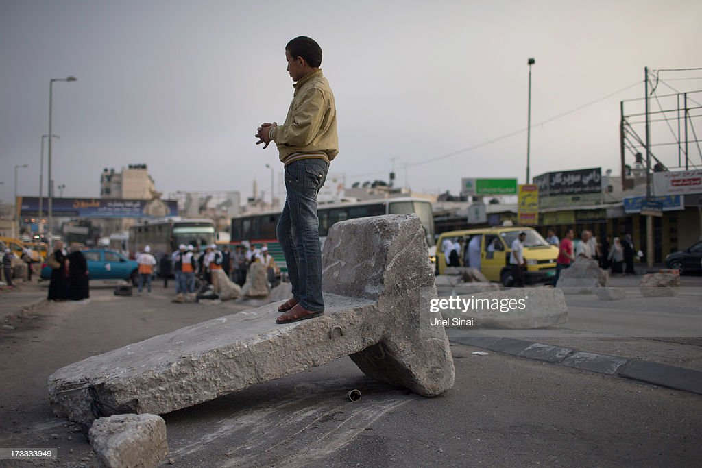 A Palestinian boy stand on a barricade as Muslim worshippers cross the Qalandia checkpoint on their way to Jerusalem on July 12, 2013 near Ramallah, West Bank. Thousands of Palestinian worshippers crossed from the West Bank into Israel to attend the first Friday prayers of Ramadan at the the Al-Aqsa mosque compound in Jerusalem.