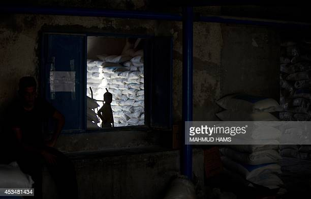 A Palestinian boy stands amidst bags of flour stored at a distribution centre of the United Nations Relief and Works Agency in Gaza City on August 11...