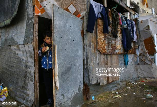 Palestinian boy stands at the entrance of his family's empoverished house near the ruins of a building destroyed during the 50day war between Israel...
