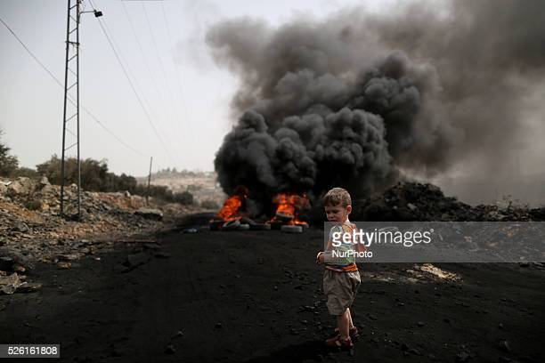 A Palestinian boy stands near a burning tyre during clashes with Israeli soldiers over the Jewish settlement of Qadomem in Kufr Qaddom village near...