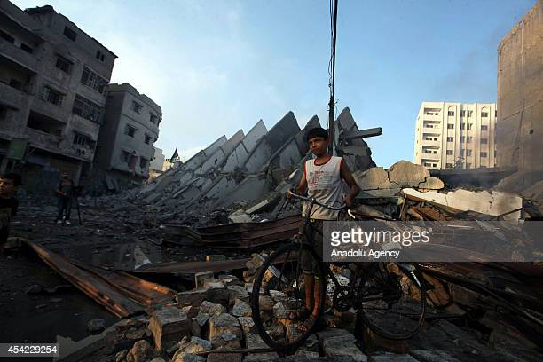 Palestinian boy stands next tho the rubble of 15storey Basha Tower one of the tallest buildings in Gaza City containing flats and offices that...