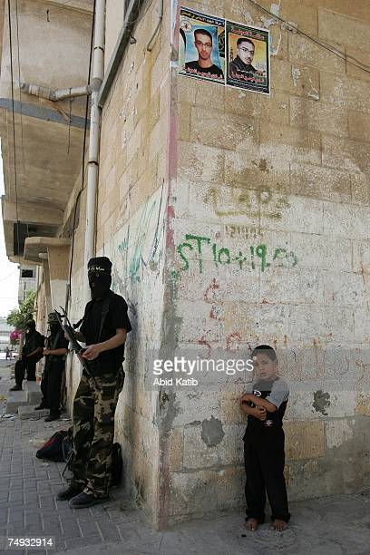 Palestinian boy stands next to masked members of the Islamic Jihad Movement while they take up position during clashes on June 27, 2007 in Gaza City,...