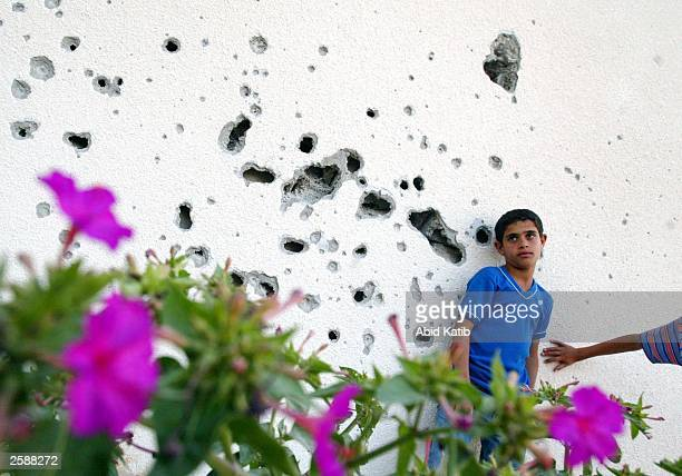 Palestinian boy stands next to wall with artillery holes made by Israeli tanks in the Yebena neighborhood of the Rafah refugee camp after a...