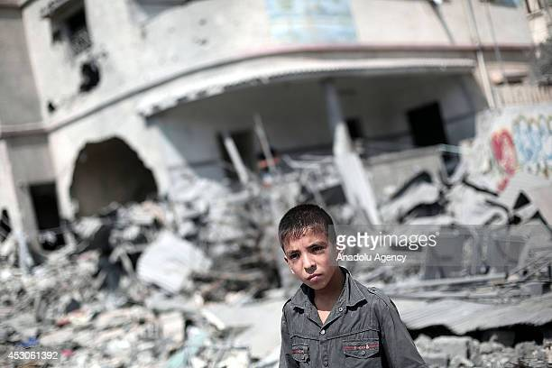 Palestinian boy stands on the rubble of a house belonging to AlNairab family after it was destroyed in Israeli airstrikes in Sabra neighborhood of...