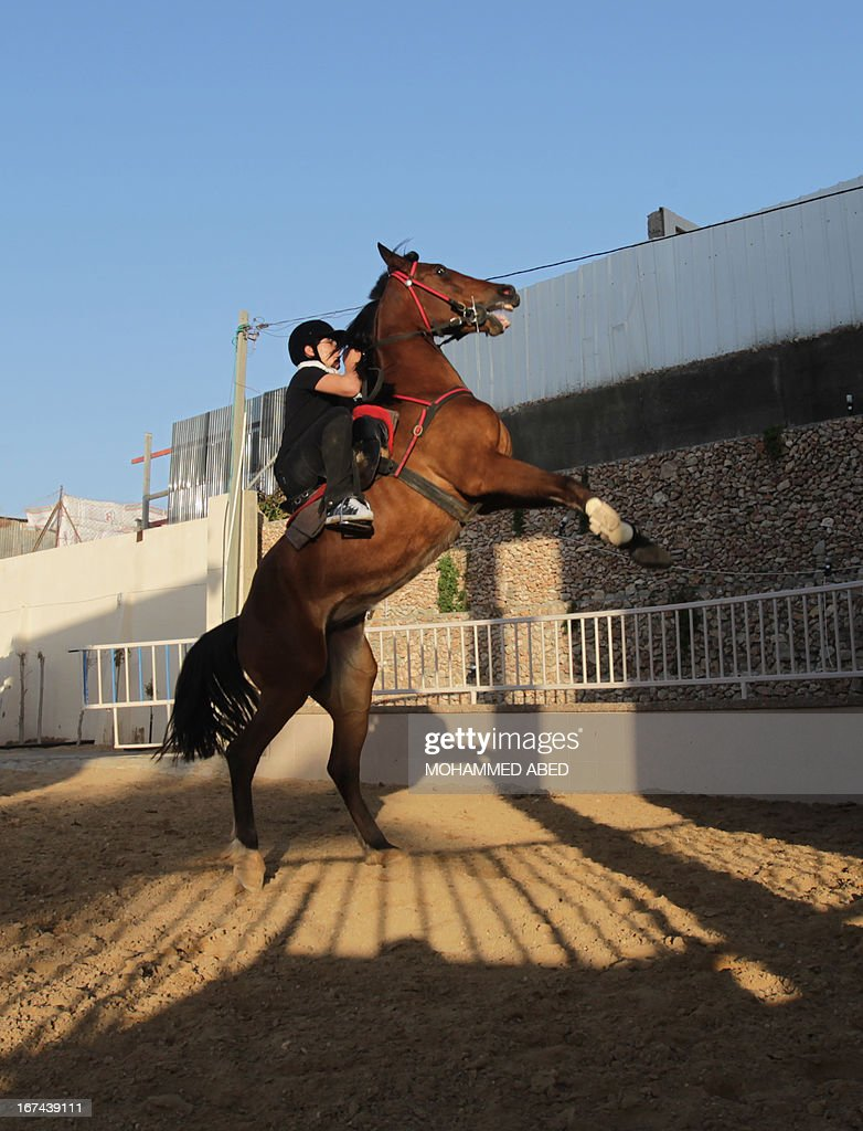 A Palestinian boy takes a horseback riding lesson on April 25, 2013 in Beit Lahia, northern of Gaza Strip.