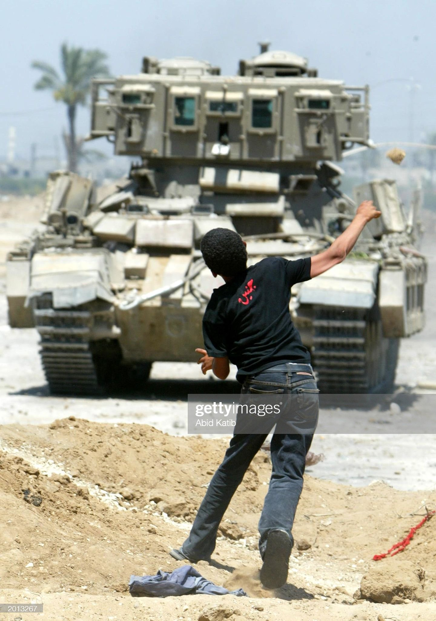 https://media.gettyimages.com/photos/palestinian-boy-throws-a-stone-at-an-israeli-tank-during-a-clash-may-picture-id2013267?s=2048x2048