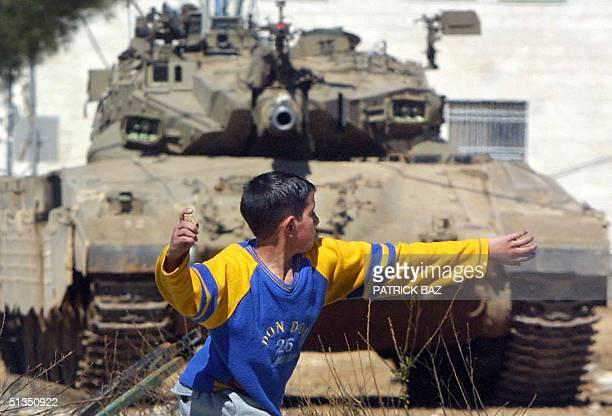 Palestinian boy throws stones an Israeli tank in Ramallah outside Palestinian Authority President Yasser Arafat's office 20 February 2002 Israel...
