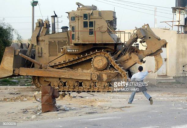 Palestinian boy throws stones at an Israeli bulldozer in front of the industrial zone at Erez crossing 27 February 2004 The Israeli army said it had...