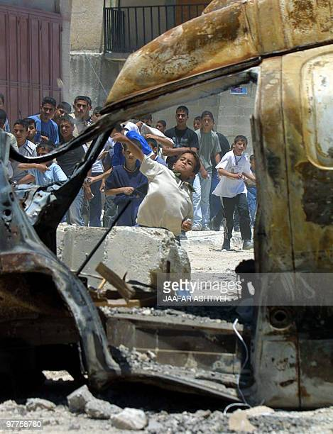 A Palestinian boy throws stones at Israeli army cars at the Balata refugee camp in the West Bank city of Nablus 04 June 2003 US President George W...