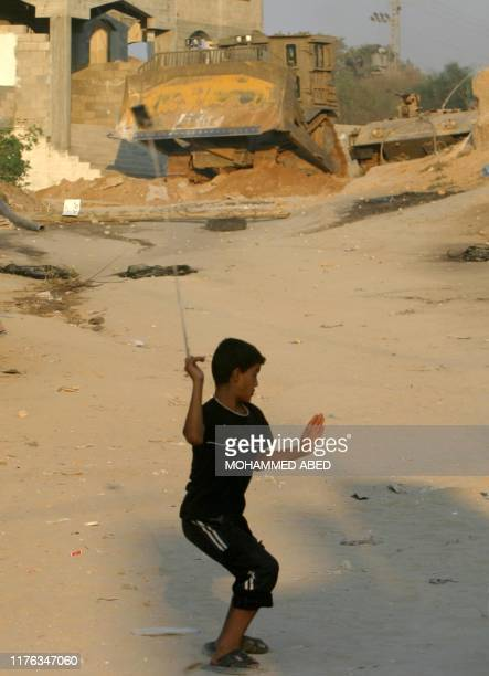 Palestinian boy uses a sling shot to throw stones at an Israeli army bulldozer during an incursion into Beit Lahia in the northern Gaza Strip 04...