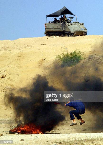 Palestinian boy uses a slingshot to throw stones towards an Israeli tank during clashes September 28 2002 in the Gaza Strip town of Bet Laheya near...