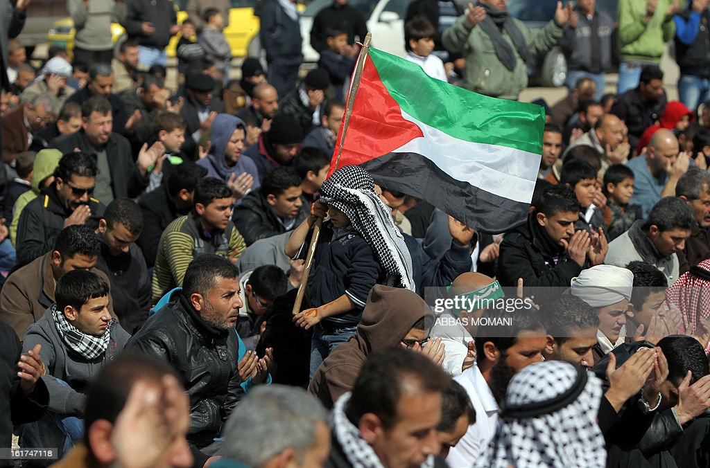 A Palestinian boy walks waving his national flag in between men performing Friday prayers in front of Ofer prison, near the West Bank city of Ramallah, prior to a demonstration in support of Palestinian detainee, Samer Issawi, who has been on hunger strike for more than 200 days, and other prisoners on hunger strike in Israeli prisons on February 15, 2013. A United Nations official on February 13, expressed concern about the wellbeing of Palestinian detainees in Israeli prisons and in particular about the condition of Issawi.