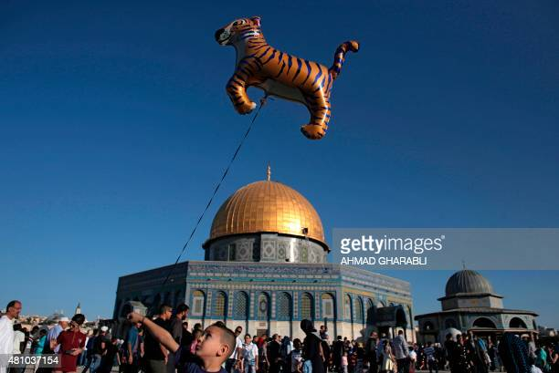 A Palestinian boy walks with a balloon in front of the Dome of Rock at the AlAqsa Mosque compound in Jerusalem's Old City on July 17 during the first...