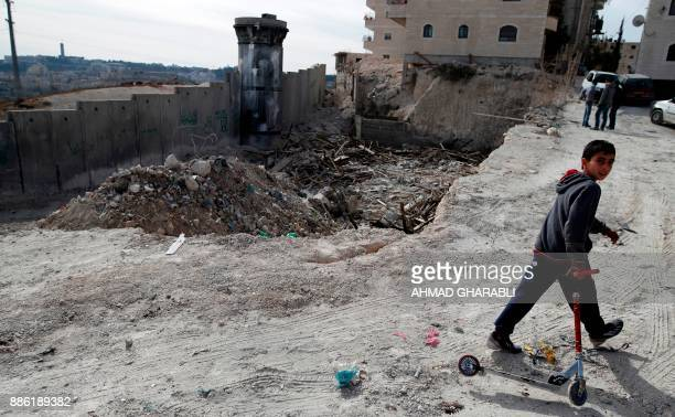 A Palestinian boy walks with his scooter past the rubble of an illegallybuilt house which was demolished by Jerusalem municipality workers in the...
