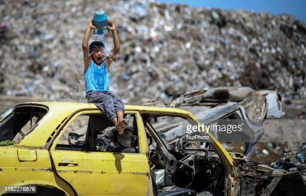 A Palestinian boy wash his body with water on a hot day in Khan Younis in the southern Gaza Strip June 27 2019