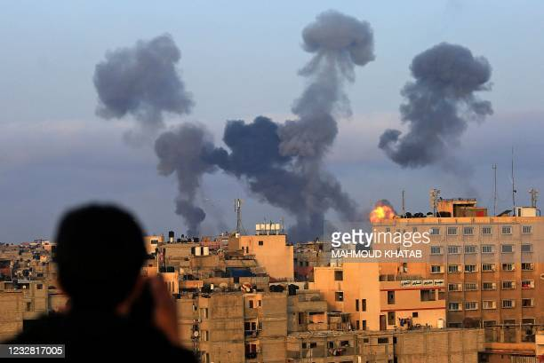 Palestinian boy watches smoke billowing from targets during Israeli airstrikes on the southern Gaza region of Khan Yunis, controlled by the Hamas...