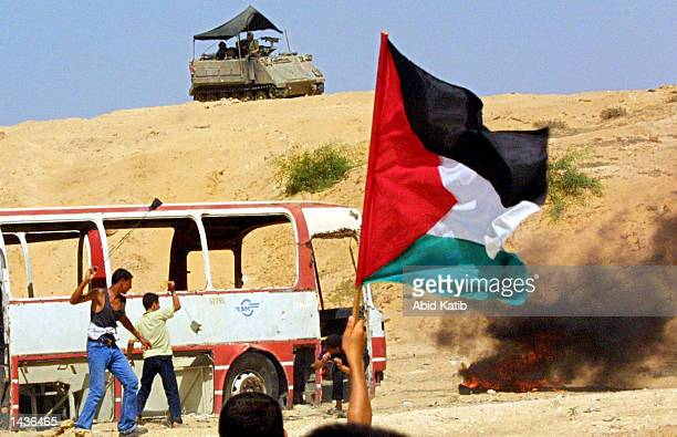 Palestinian boy waves his national flag as youths use slingshots to throw stones towards an Israeli tank during clashes September 28 2002 in the Gaza...