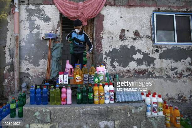 Palestinian boy wearing a protective mask sets cleaning tools and disinfectants for sale amid concerns over the spread of the coronavirus epidemic,...
