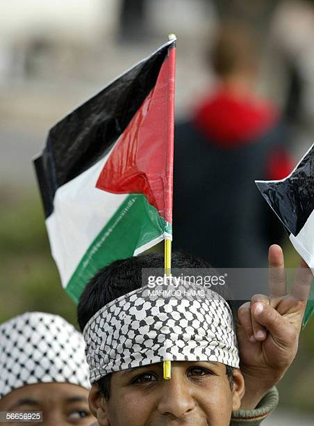Palestinian boy wears a bandana in the colours of a Kefiyeh with a national flag sticking out as he attends a rally supporting a plea against people...