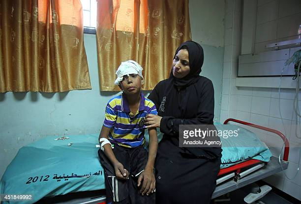 Palestinian boy who was injured in an Israeli airstrike sits next to his mother after receiving treatment at a hospital in Khan Younis southern Gaza...