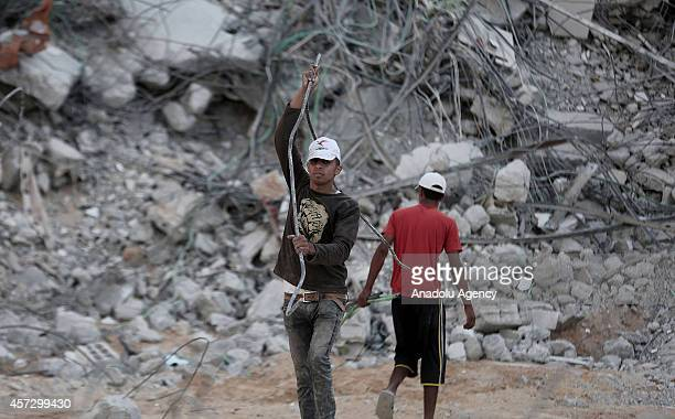 Palestinian boys collect reinforcing bars among the debris of buildings destroyed during the Israeli attacks to sell them to construction workers as...