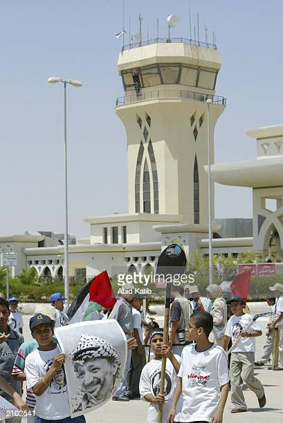 Palestinians hold posters of their leader shovels and their national flag during a protest on June 22 2003 at Gaza international Airport Gaza Strip...