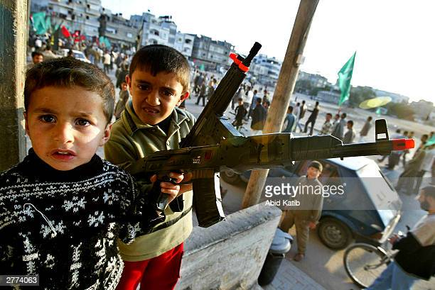 Palestinian boys hold toy guns while protesters attend a demonstration against the Geneva Accord by different groups on December 1, 2003 in the...