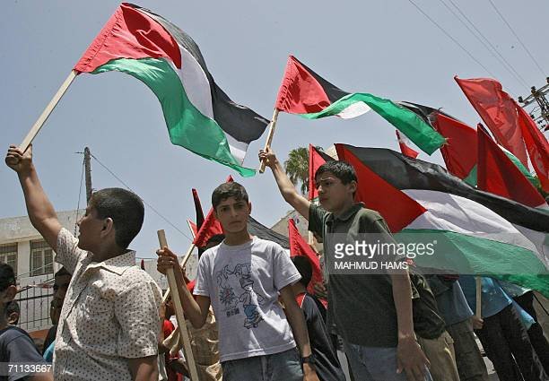 Palestinian boys hold up national flags during a demonstration against internal fighting among Palestinian factions in Gaza City 06 June 2006 Five...