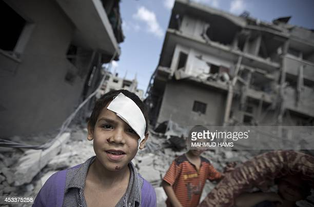 Palestinian boys look on as they inspect the rubble of a house after it was destroyed by an Israeli military strike in the Jabalia refugee camp in...