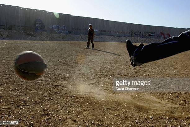 Palestinian boys play a pickup game of soccer using an old basketball on a dusty field alongside Israel's separation barrier June 20 2006 in the West...