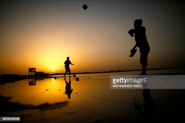 TOPSHOT Palestinian boys play at the beach as the sun sets in Gaza City on January 11 2018 / AFP PHOTO / MOHAMMED ABED
