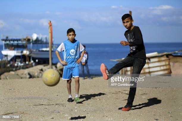 Palestinian boys play football in Gaza City on November 3 2017 / AFP PHOTO / MOHAMMED ABED