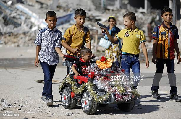 Palestinian boys play on a street on October 4 2014 in the northern district of Beit Hanun in the Gaza Strip during the Muslim holiday of Eid alAdha...